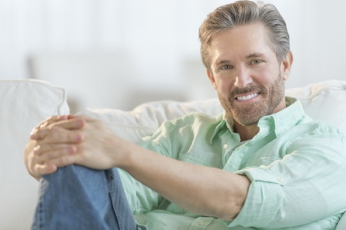 Portrait of handsome mature man relaxing on sofa at home