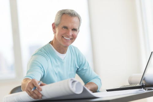 Portrait of happy male architect holding blueprint at desk